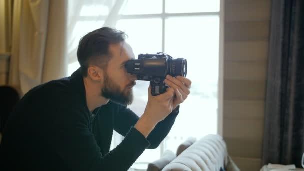 Fotografo che compongono e incornicia immagine, messa a fuoco e ripresa con fotocamera a pellicola medio formato in studio, artista maschio professionista lavorando con obiettivo grandangolare ritratto