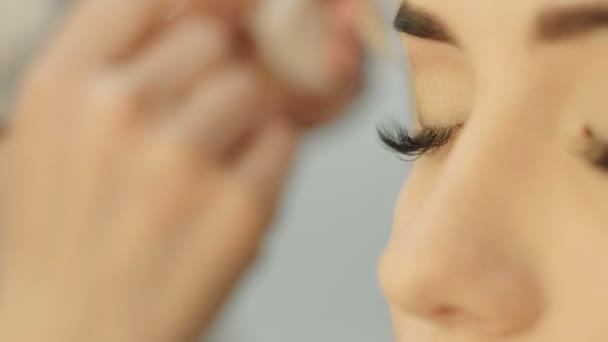 Profesionální oční makeup umělec použití eyeshadow powder. Krásná žena tvář. Dokonalý make-up. Módní krása. Řasy. Detailní záběr