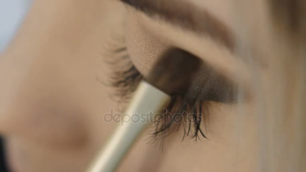 Professional Eye makeup artist applying eyeshadow powder. Beautiful woman face. Perfect makeup. Beauty fashion. Eyelashes. Macro shot and slow motion