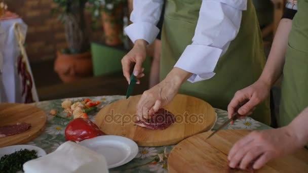 Více lidí plátky syrové maso na dřevěné desce