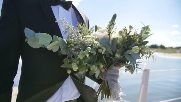 groom holding wedding bouquet in front of the lake in slow motion