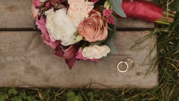 Wedding rings and wedding bouquet at wooden and grass surface