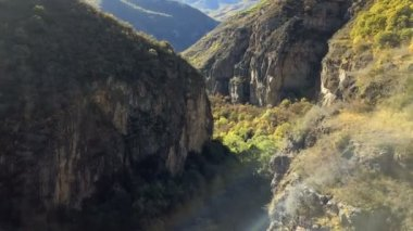 4K aerial shot mountain gorge and cliff with sun leaks
