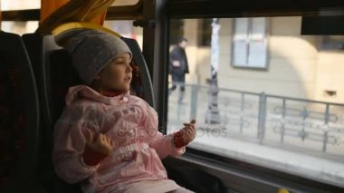 Little Blonde Girl in a pink jacket, Kid is Sitting in a Bus Cabin. Sitting on Her Seat and Looking through the Glass Window.