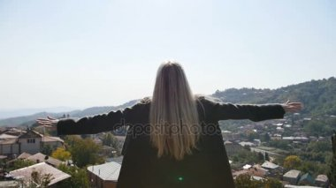 Young woman standing raised raising up hands looking at village and peaks mountains background amazing landscape. Satisfied fresh air breathing girl full back view.