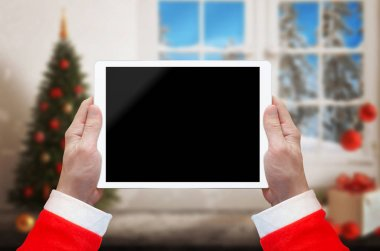Santa Claus work on tablet with isolated screen for interface promotion. Christmas time with decorations.