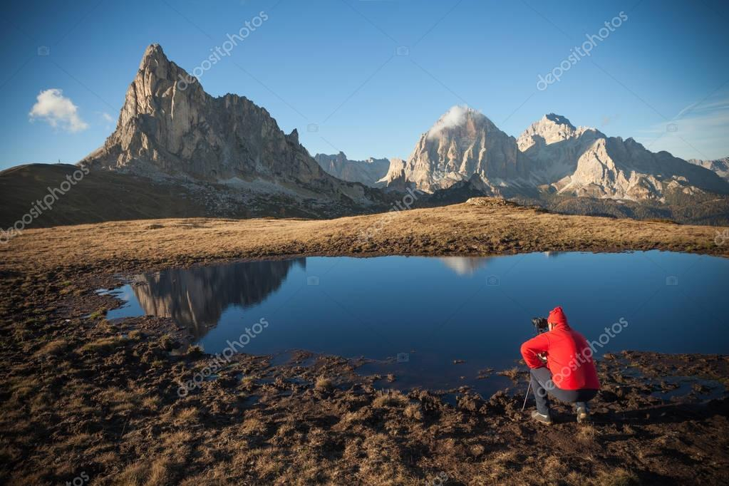 Photographer next to a small mountain lake in Dolomites