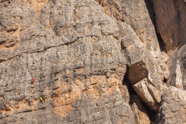 Rock climbers in action over a vertical cliff in the Cinque Torri area in Dolomites