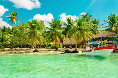 Amazing exotic palm tree beach with colorful boat, Dominican Republic