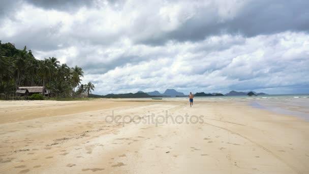 uomo che corre sulla spiaggia.