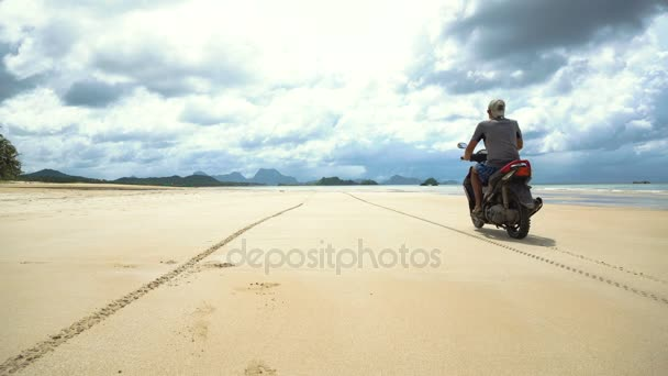 Muž řídil motocykl na pláži