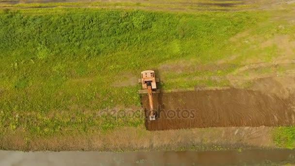 Rypadlo kopat příkop v poli. Letecké video