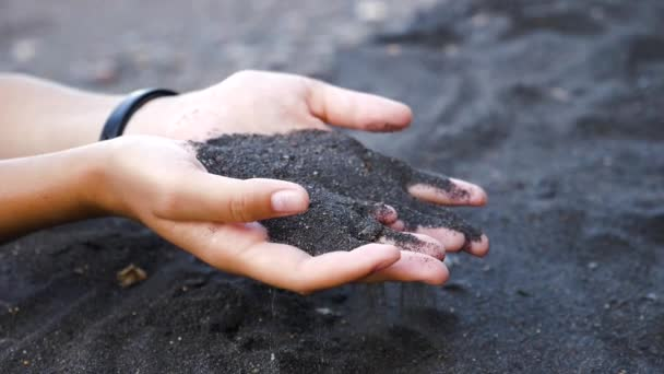 Hand pours the sand.