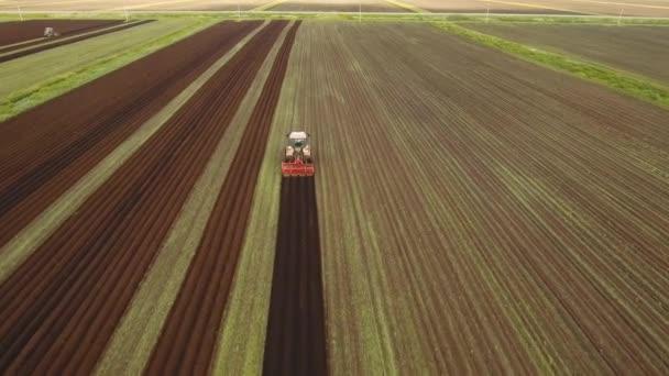 Traktor obdělává půdu na poli.