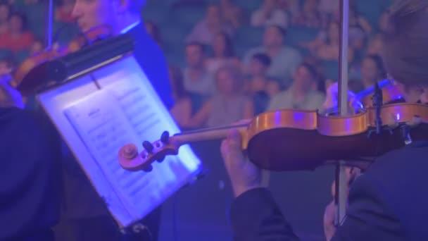 Rock Symphony Concert Kiew Geiger well-dressed Männer sind spielen Geigen in Blue Light Music Hall ist voll von Zuschauern Musikbücher über Stände Dark Hall