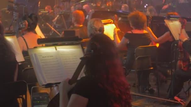 Rock Symphony Concert Kiew Cellisten Geiger beginnen zu spielen, die ihre Teil-Musiker spielen in eine Zeilen-Musikbücher steht Beleuchtung in der Halle sitzen