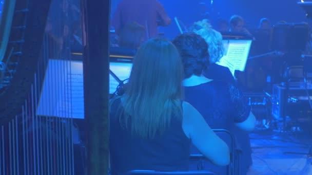 Hudebníci hrát housle harfeníka s Bun Panorama orchestr řetězce nástrojů modré lampy Dark Hall knih stojí hudebník zadek Rock symfonie