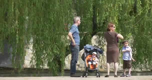 Den města v Opolském žena s kamerou si vybere místo pro pořizování obrázků vypadá kolem otce matka a dvě děti tráví víkendy v parku u jezera