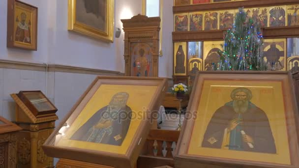 una fila di splendide icone in una cattedrale ortodossa e una donna baciandola e pregare non lontano da uniconostasi alta a Kiev