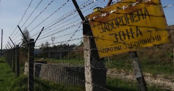 Düster aussehender Stacheldrahtzaun und Wachturm mit gelbem Verbotsschild, der ein Öllager in der Ukraine umgibt