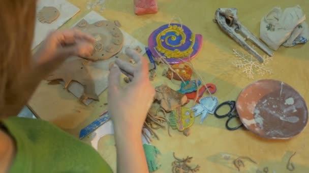 Vysoce kvalifikované paní dělá legrační deska hlíny na dřevěném prkénku, pomocí některé konkrétní nástroj, a holčička je to její vlastní dar