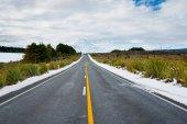 Long yellow center line along road through winter landscape lead