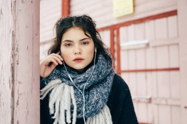 A cute girl sits and listens to music in the winter season