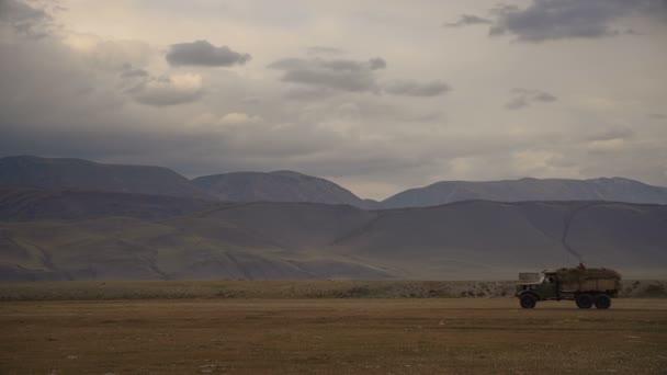 Nákladní automobil jízdy přes pole s kopce a hory v pozadí v denní za zatažené obloze