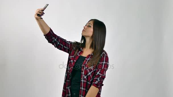 Krásná mladá žena dělá selfie, na bílém pozadí