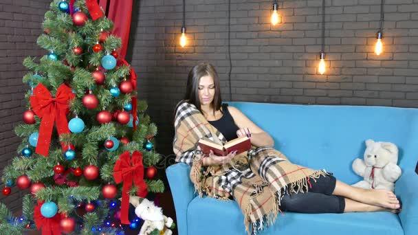 mladá žena sedí na gauči, zabalený do deky a čtení knihy