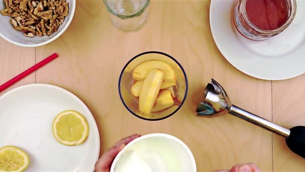 Putting cheese over apples into the blender for a healthy and nutritious smoothie