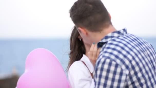 Boldog pár csók a szerelem gazdaság ballonok színes szívek a kezükben