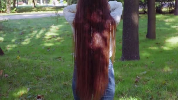 Woman flutter her luxury long hair then turn aroung and smile into camera
