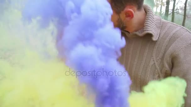 Man and woman kissing and holding bright yellow and purple smoke. In the forest
