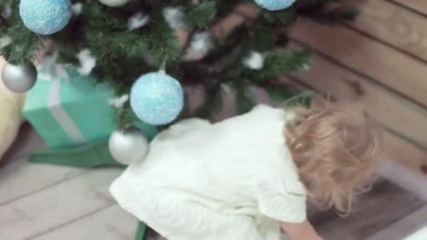 kleines blondes süßes Mädchen sucht Geschenke unter dem Weihnachtsbaum