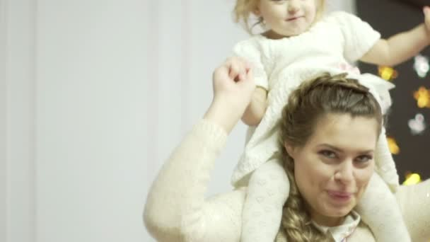 Young mother is playing with her little daugther. Little cute baby girl sits on her mothers shoulders