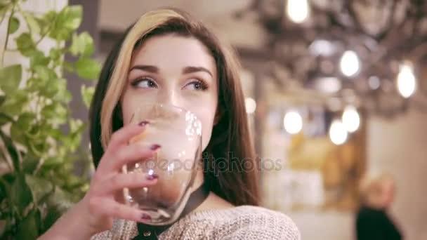 Krásná mladá brunetka žena pít horké kakao v zařízené kavárny