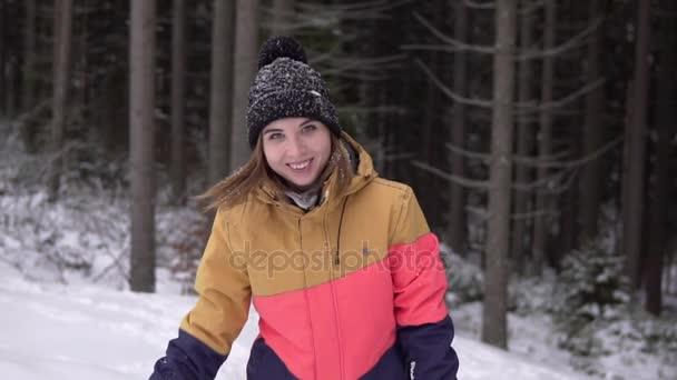 Ženy jdou k fotoaparátu v zimě sníh lese a mává rukou Ahoj