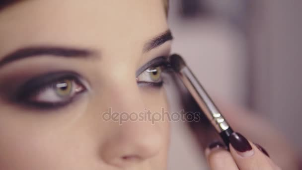 Použití očních stínů makeup na modely očí vizážistka. Zblízka pohled. Kouřové oči. Levý pohled