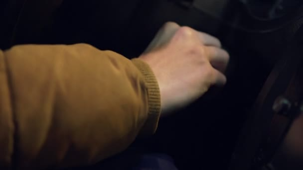 Man turning ignition key in car. Close up view
