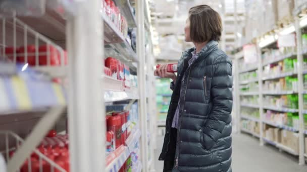 Young woman shopping in grocery chosing products