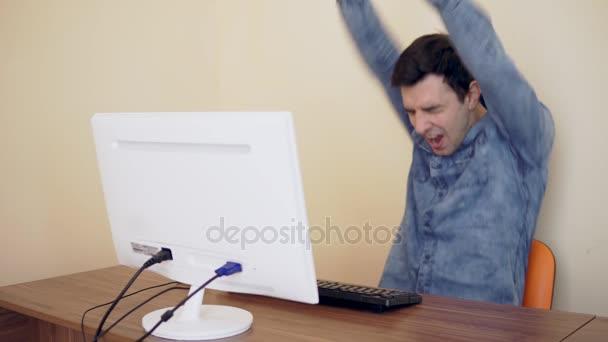 Šťastný mladý muž pracoval na počítači v kanceláři a získání dobré zprávy. Neočekávaný úspěch