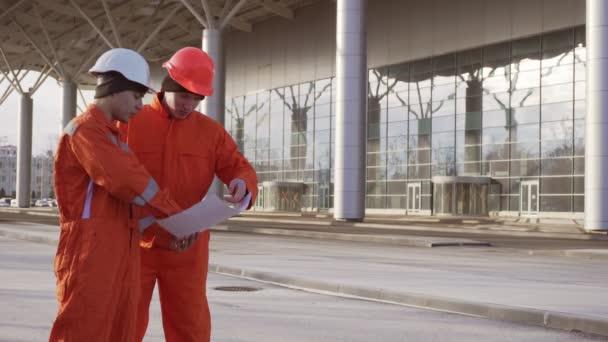 Dva stavební dělníci v orange jednotným a Havířské dívá přes plány společně. Budova v pozadí