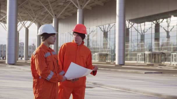 Two construction workers in orange uniform and hardhats examining the constructed building together. Teamwork concept