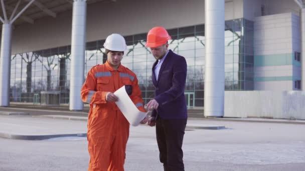 Giovane architetto in un vestito nero esaminando loggetto edilizio con operaio edile in arancione uniforme e casco. Essi incontrarsi presso loggetto bulding e che agitano le mani.