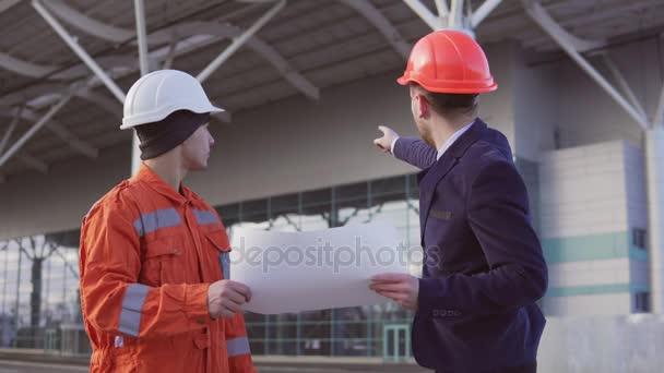 Mladí vedoucí projektu v černém obleku, zkoumá stavební objekt s stavební dělník v orange jednotné a helmu