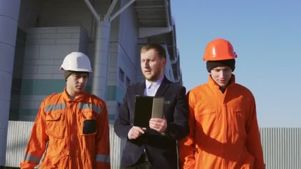Manager in a suit and two workers in orange uniform and helmets are walking through building facility. Shot in 4K