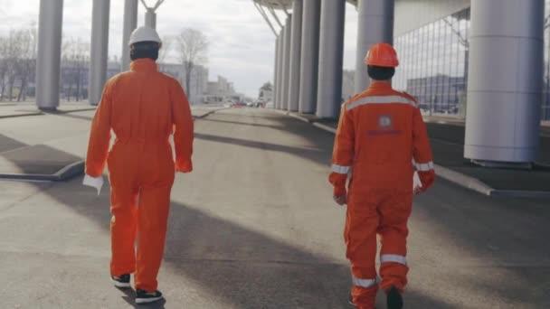 Két boldog építőmunkások narancssárga egységes és sisakok, séta, és ugrás a együtt.