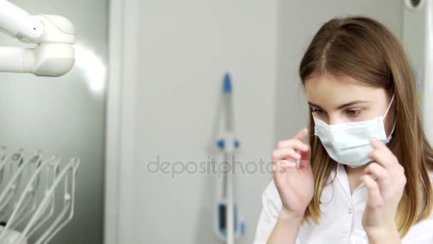 Zblízka se z mladých žen zubař nosit ochranné brýle v kabinetu zubního lékaře. Brownhaired žena v lékařské masku a ochranné brýle, příprava na postupu. Kavkazská zubní chirurg