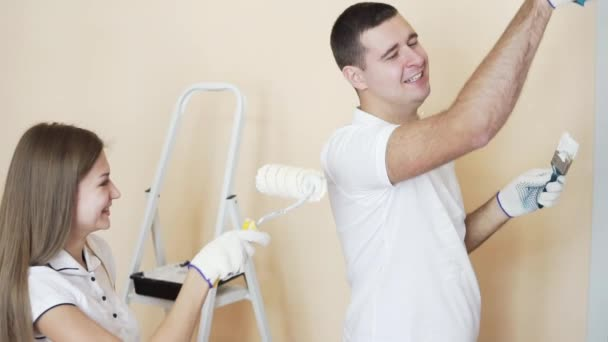 Fröhliches Junges Paar In Weißen Hemden Schmücken Ihre Neue Wohnung. Junger  Mann Und Frau Sind